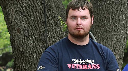 veteran student in front of tree