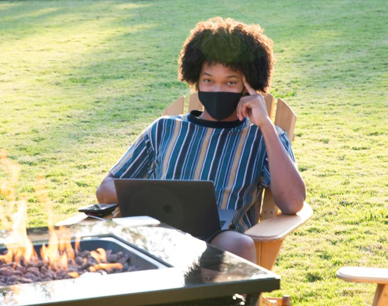 student wearing a mask studying with a laptop sitting by a fire pit