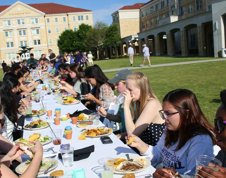 Students eating at a large table in the campus commons at TCU's Common Table event
