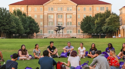 Students sitting in a circle on commons lawn area